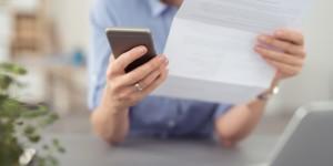 frau schaut auf einen brief und tippt auf ihr mobiltelefon